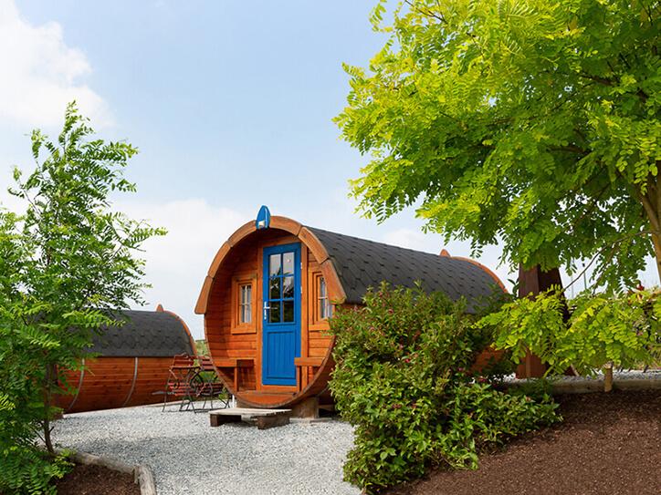 Schlaffass mit blauer Tür eingebettet in die Natur