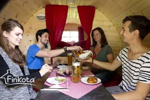 Glückliche Gruppe macht Brotzeit mit Bier im Schlaffass